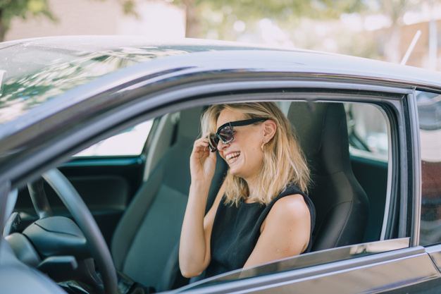 blonde-young-woman-sitting-car-laughing_23-2148066787