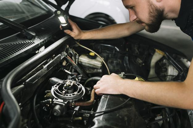 technician-checking-car-motor_23-2147897986
